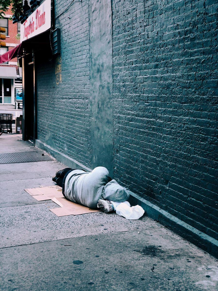 Person sleeping on sidewalk