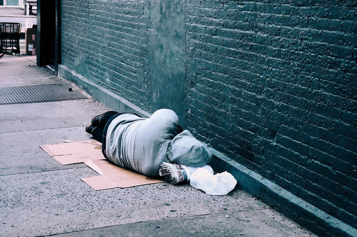 Person sleeping on sidewalk