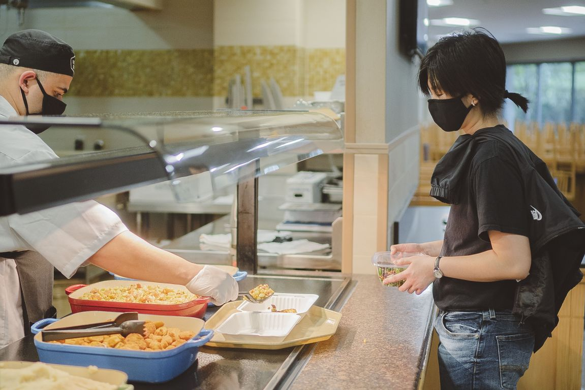 Dining hall staff person, left, wearing a mask serves food to a student, right, also wearing a mask.