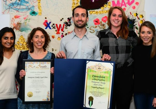 Click to open the large image: Members of legal clinic holding commendations