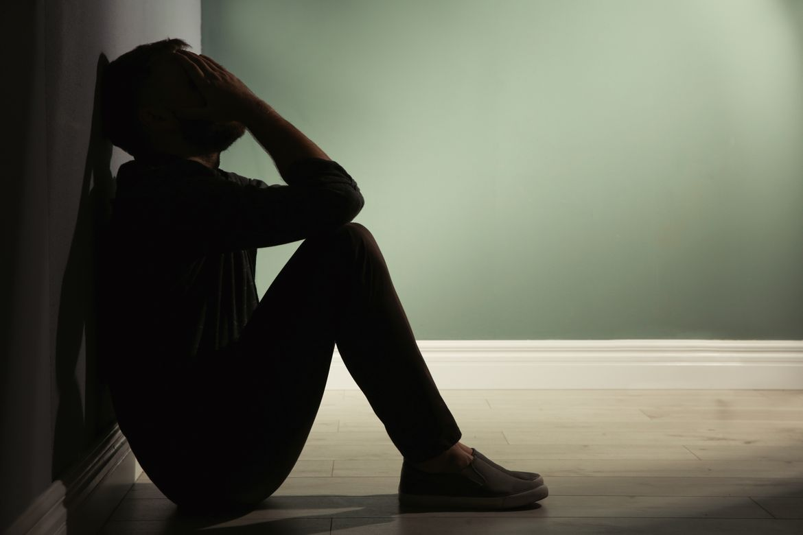 Depressed man leaning against wall