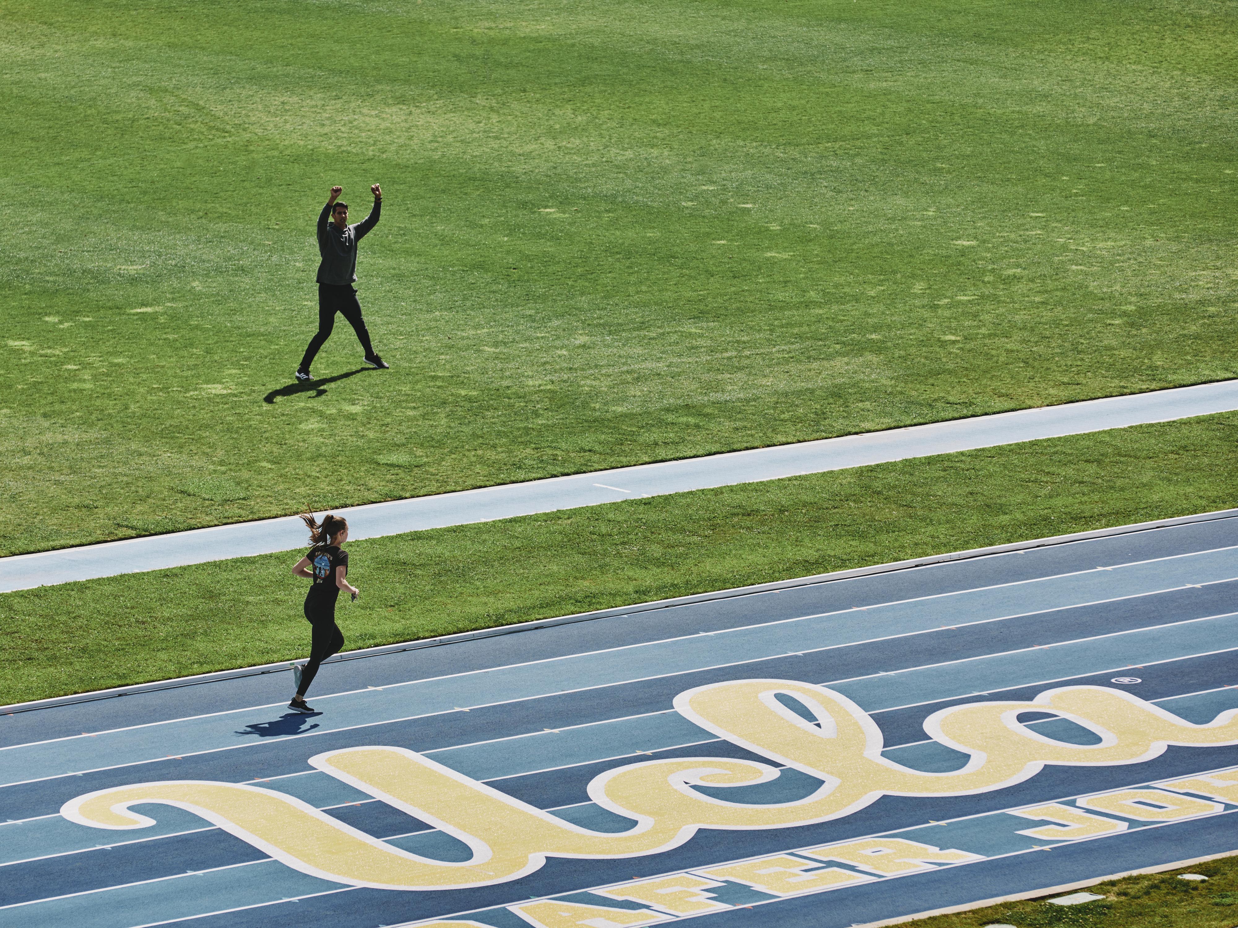 Woman runs around the track at UCLA's Drake Stadium.