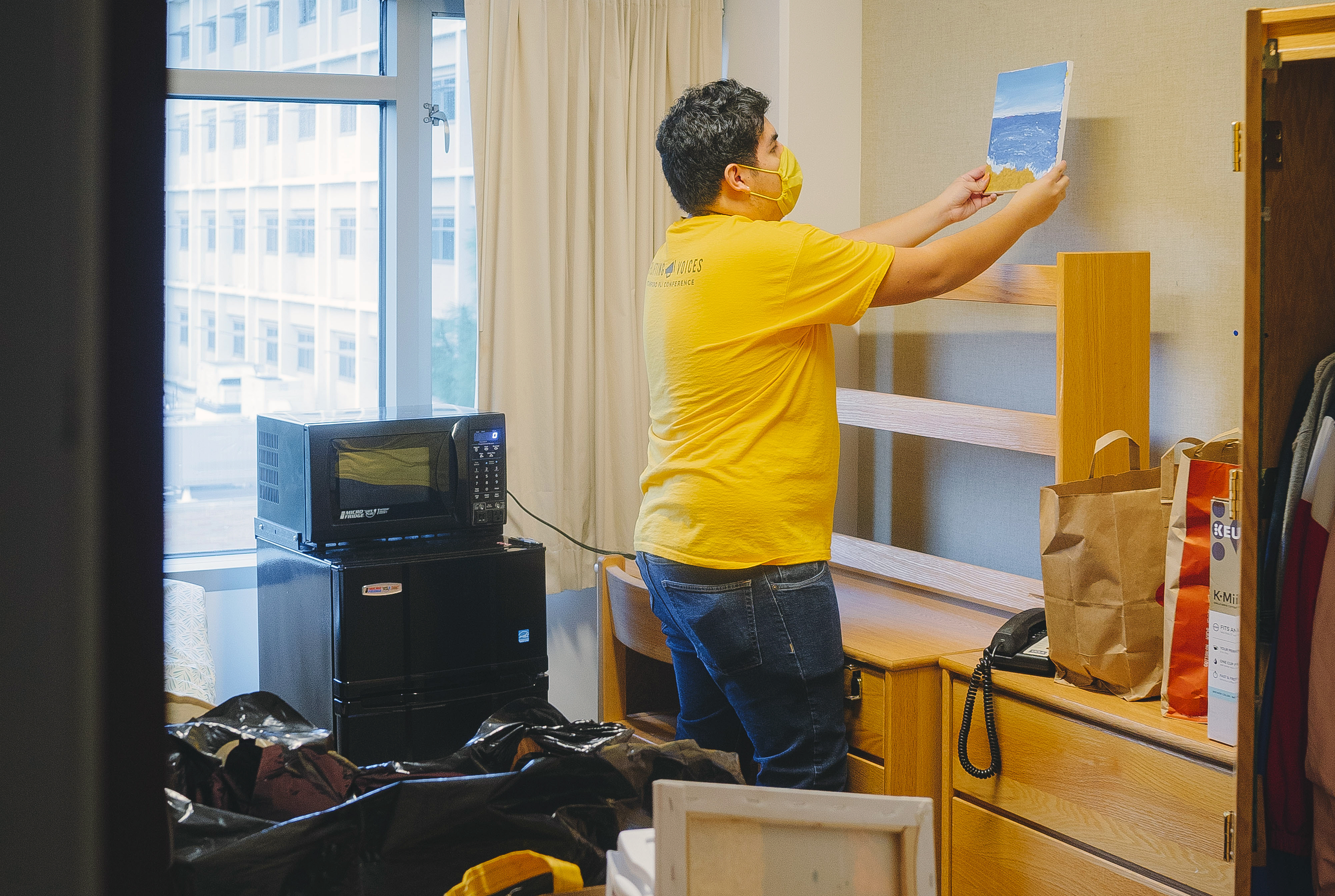 Gustavo De Santiago Reyes hanging a picture in his room