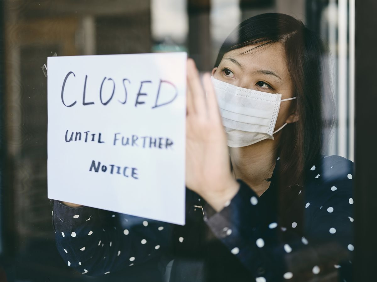Woman holding 'closed' sign up to window