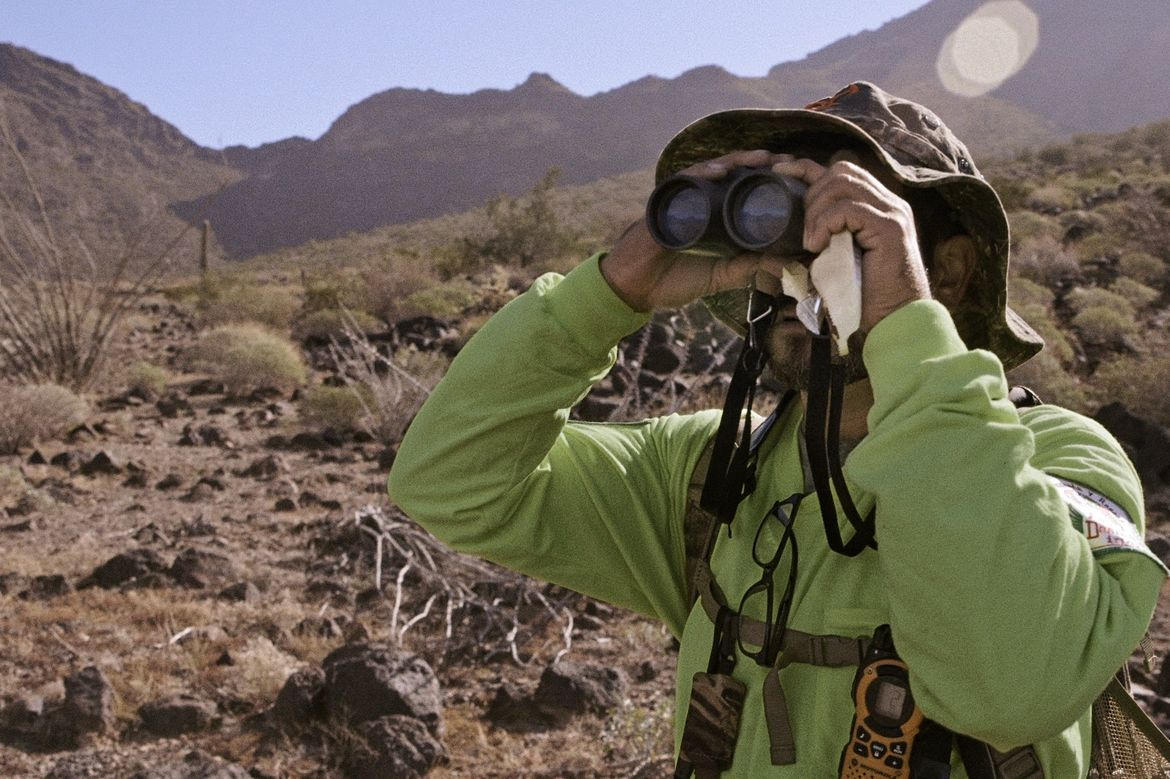 Man scans desert with binoculars