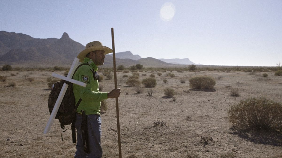Man in desert with cross
