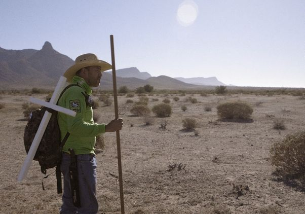 Man with cross in desert