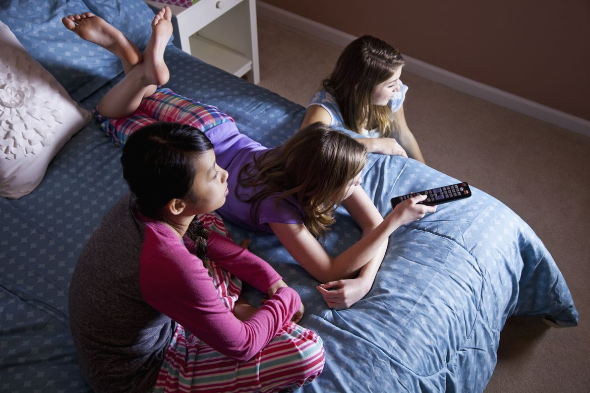 Girls on bed watching TV