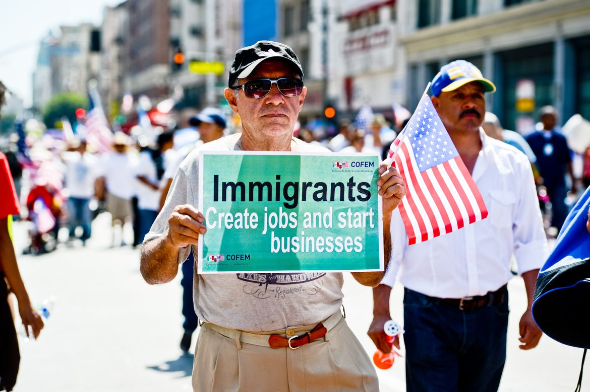 Man with immigrants create jobs sign