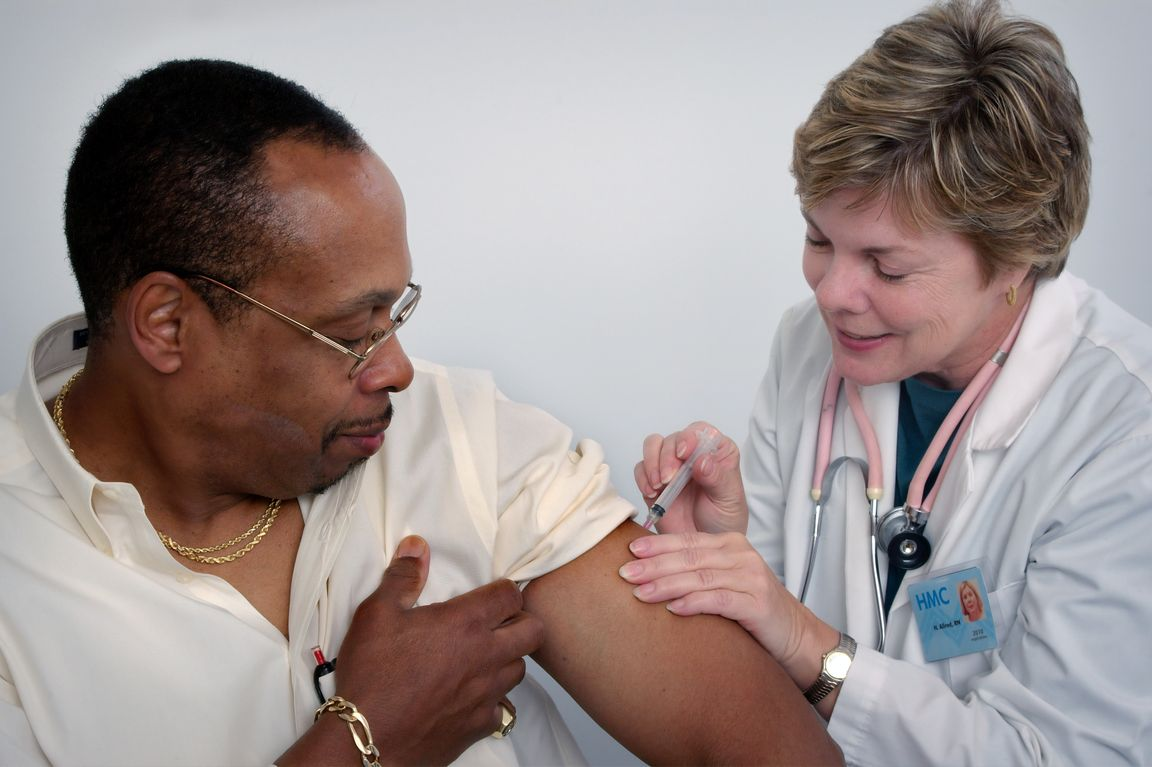 Doctor administering shot to patient