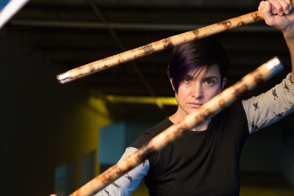 Janet O'Shea holding sticks used in martial arts