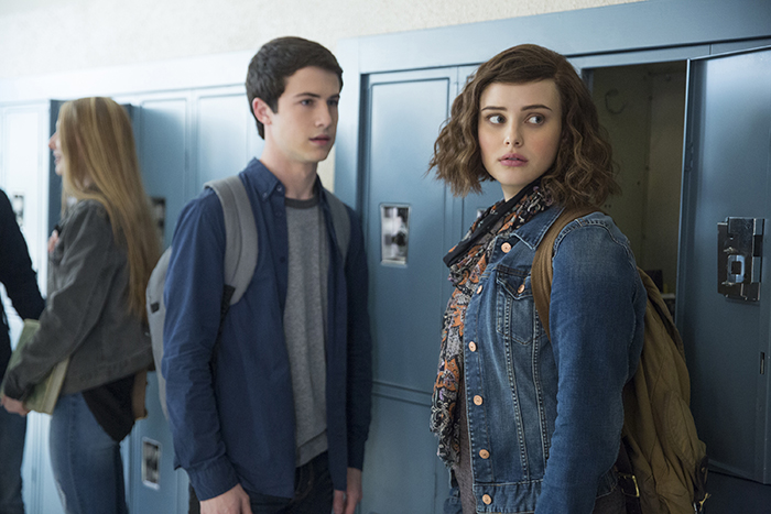 Two characters from Netflix program in front of school lockers.