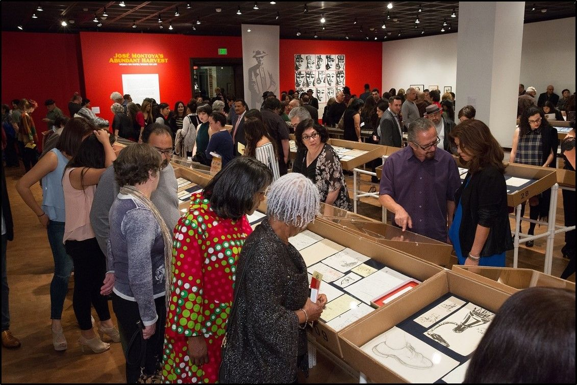 """A crowd at the Fowler Museum at UCLA on the opening night for """"José Montoya's Abundant Harvest: Works on Paper/Works on Life,"""" which UCLA professor Chon Noriega helped curate."""