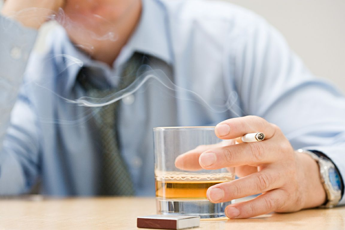 Man at table with cigarette and drink
