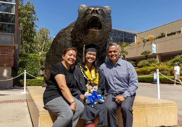 Click to open the large image: UCLA Commencement 2021 - Family at the Bruin statue