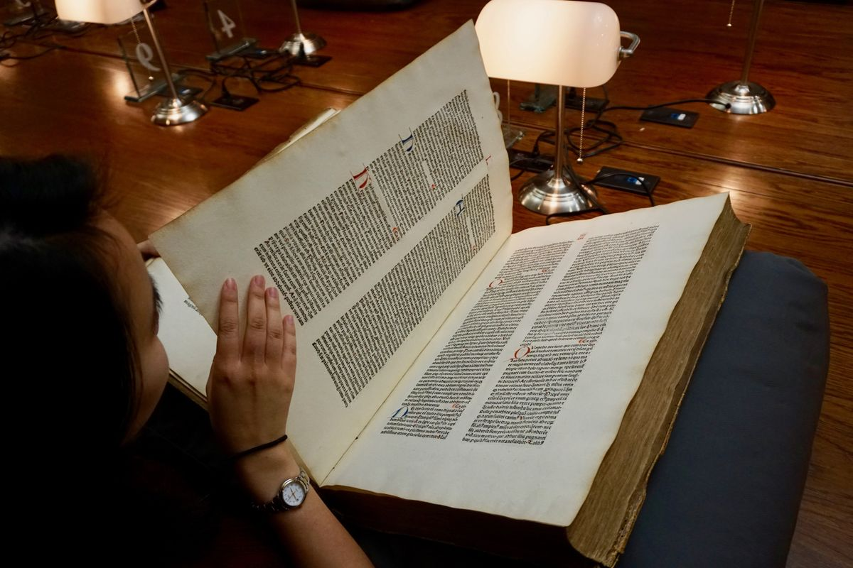 Student reading old book in special collections reading room