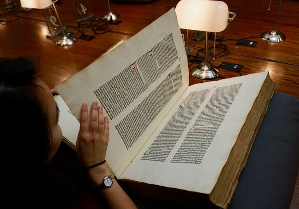 Click to open the large image: Student reading old book in special collections reading room