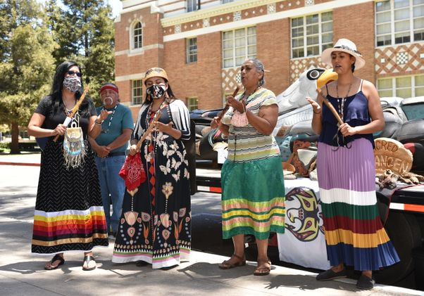 Click to open the large image: Lummi totem at UCLA with singers