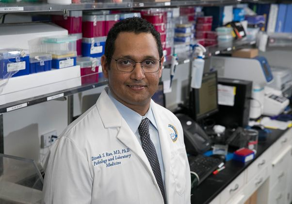 Dr. Dinesh Rao in white lab coat in his laboratory