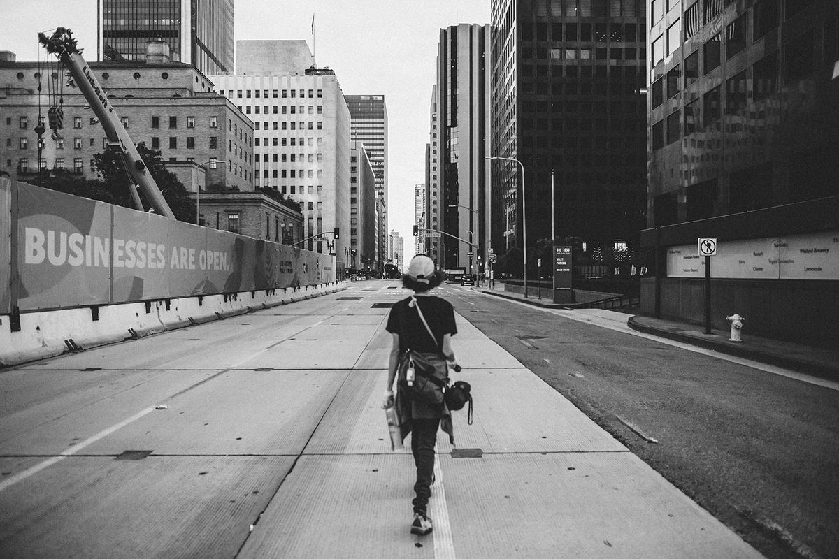 """Black and white photo of a woman walking through an empty downtown Los Angeles from the film """"Last Light"""""""