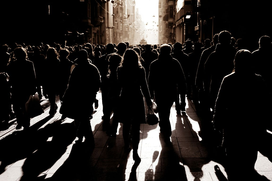 Silouhette of people walking on busy street