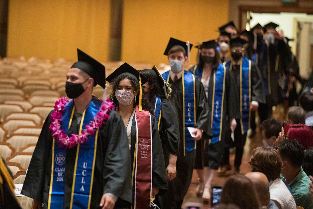 Graduates from the class of 2020 have a procession into Royce Hall for a makeup commencement ceremony.