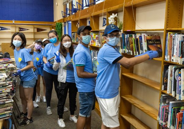 Click to open the large image: UCLA Volunteer Day 2021 - Students re-shelving books
