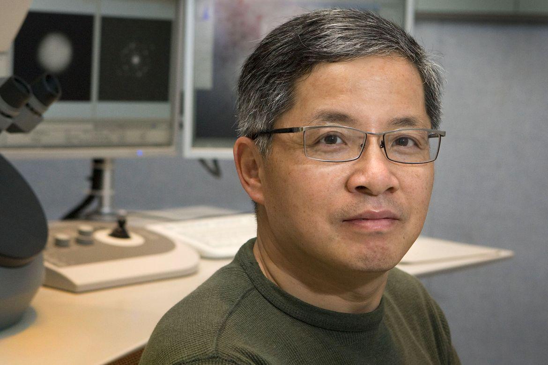 "Jianwei ""John"" Miao photo at desk with computer screens and microscope"