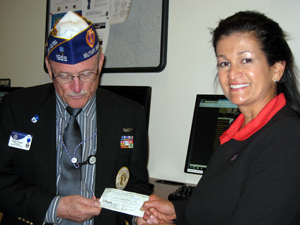 Roger D. Newall, Commander of the Dept. of New Mexico Military Order of the Purple Heart presents UNM Veteran's Resource Center Director Mandy Dykman with a check.