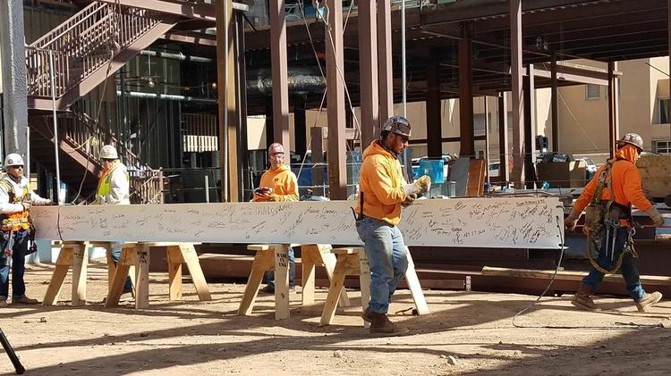 Workers secure beam before raising