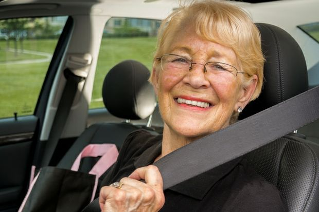 Smiling senior mature driver holding seatbelt