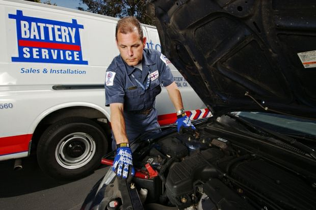 battery service tech with truck behind checks battery