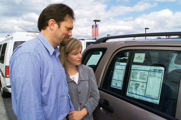couple looks at mileage sticker