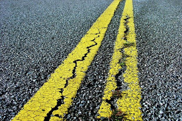 double yellow road line with cracks