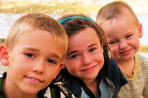 three carseat age kids smile at camera