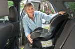 Woman grandma puts carseat in car