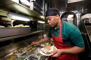 Seaman Mykal Martin helps serve the first meal on board the USS New Mexico, SSN 779. Photo by John Whalen.