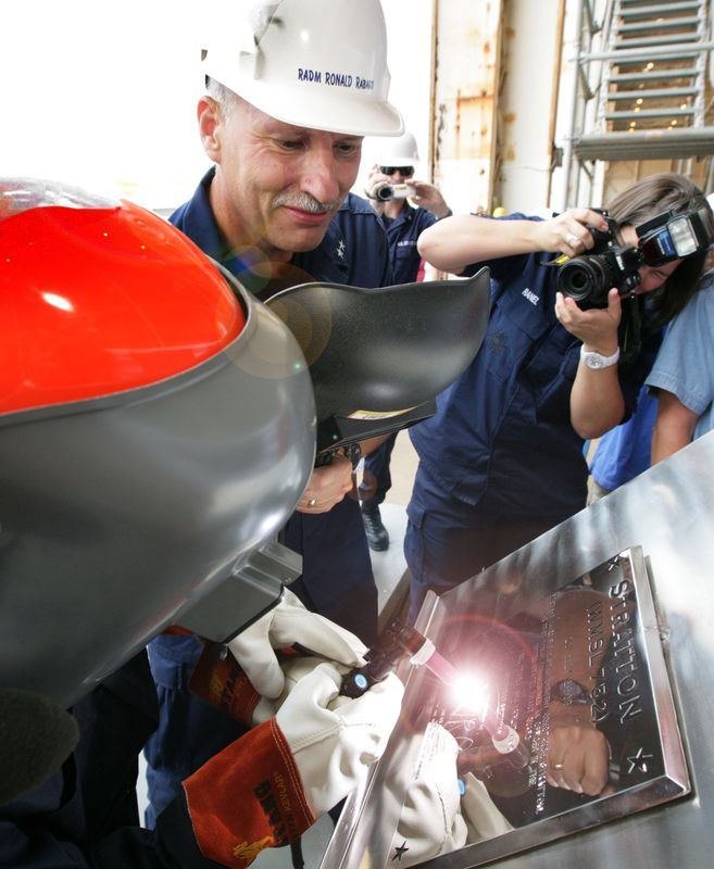 U.S. Coast Guard Rear Adm. Ronald Rabago, the Coast Guard's assistant commandant for acquisition, observes as Northrop Grumman Shipbuilding welder Julie