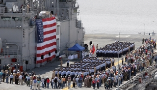 U.S. Navy Sailors and Northrop Grumman shipbuilders together manned the flight deck of Makin Island (LHD 8)
