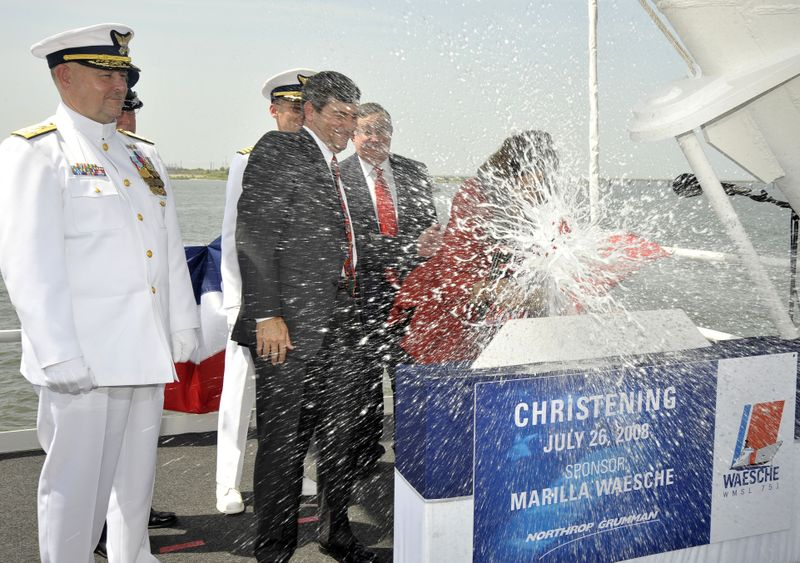 WASHED IN TRADITION: Marilla Waesche Pivonka (right), ship's sponsor, breaks a traditional bottle spraying the bow and platform guests at the christening of the Northrop Grumman-built U.S. Coast Guard National Security Cutter Waesche (WMSL 751).