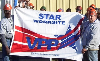 Shipfitters Al Layton, left, and Sam McPherson, right, hold up the new Voluntary Protection Program (VPP) flag donated by OSHA