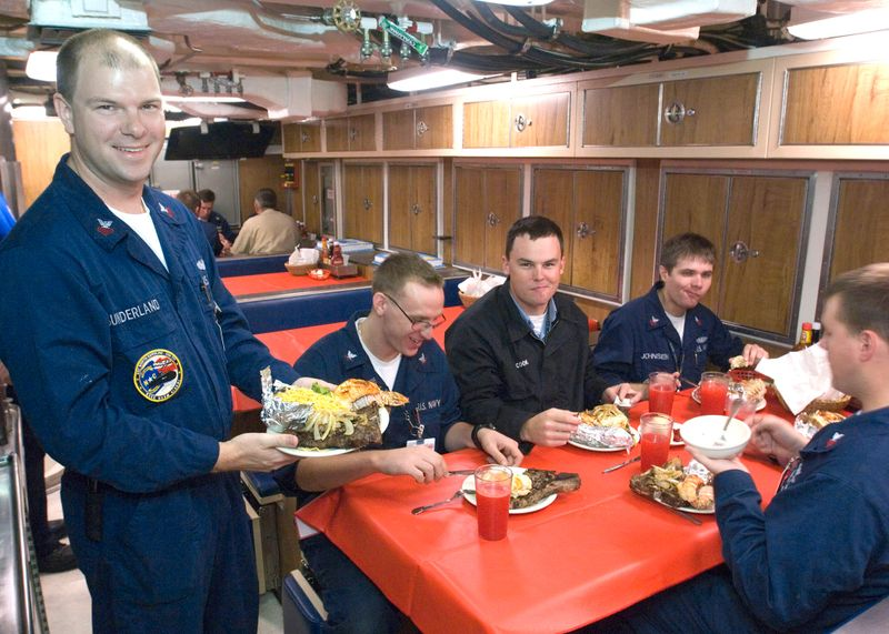 Crewmember Martin Sunderland holds up his plate of steak and lobster.