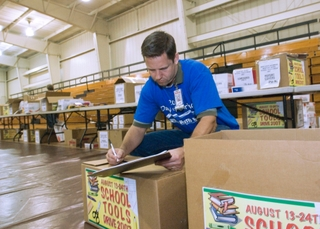 "Northrop Grumman Newport News employee Gary Guye prepares boxes of ""school tools"""
