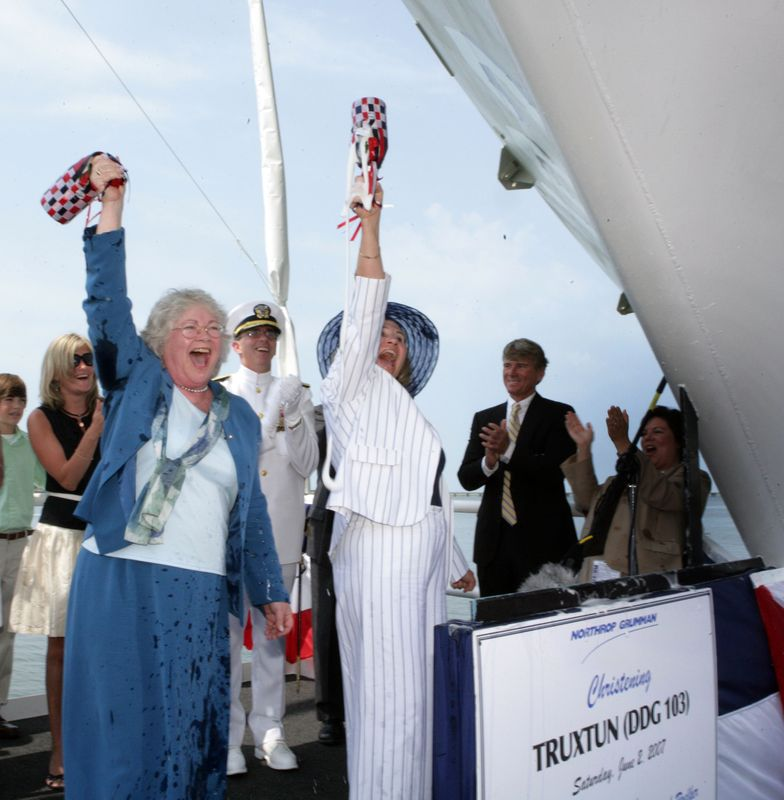 Ship sponsors Susan Scott Martin, left, and Carol Leigh Roelker, right, raise their commemorative bottles of champagne after breaking them across the bow of the Northrop Grumman-built Truxtun (DDG 103)