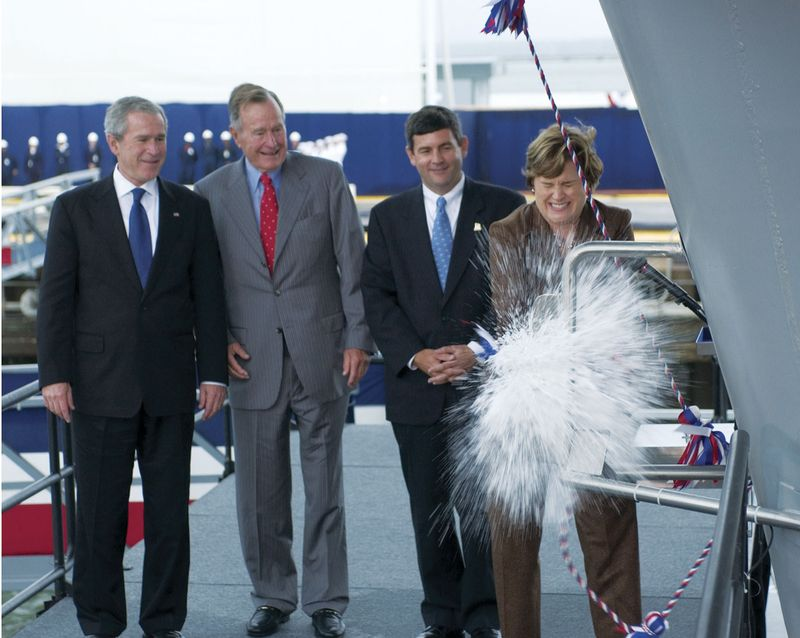 (Left to right) President George W. Bush, Former President George H.W. Bush, and Mike Petters, president, Northrop Grumman Newport News, look on as Ships' Sponsor Doro Bush Koch christens CVN 77, the aircraft carrier George H.W. Bush.