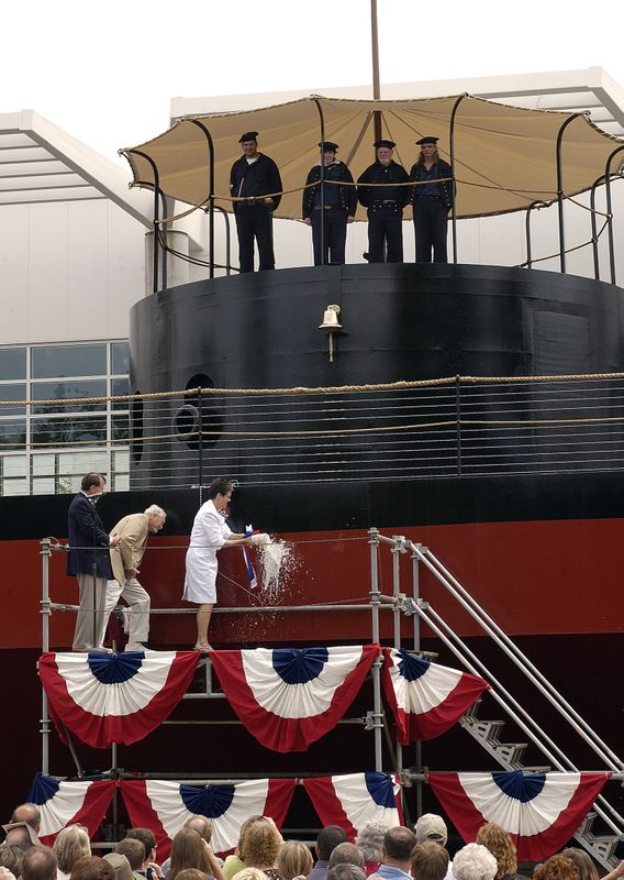 (From left) The Mariners' Museum President and CEO John Hightower and famed author Clive Cussler lean in to watch as Nancy Petters, the ship's sponsor and wife of Northrop Grumman Newport News President Mike Petters, christens the USS Monitor replica