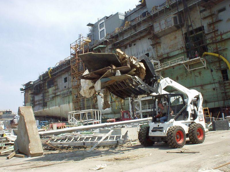 Northrop Grumman's Owen McLeod clears storm debris from the dry dock alongside the large-deck amphibious carrier Makin Island (LHD 8)