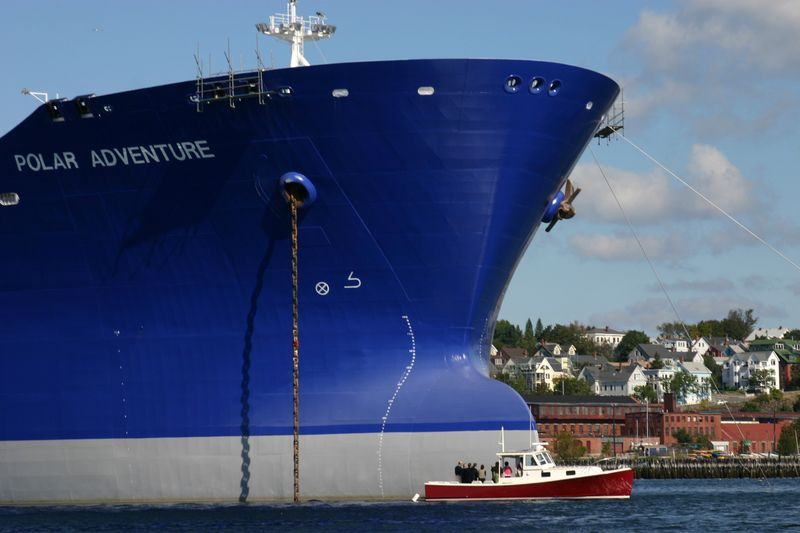A fishing vessel is dwarfed by the giant bow of the tanker Polar Adventure