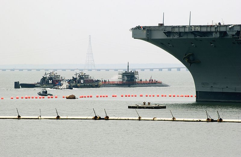 The submarine USS Hyman G. Rickover is dwarfed by the USS Dwight D. Eisenhower's bow