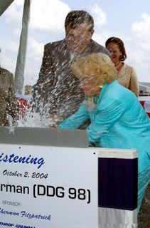 SMASHING HONORS -- Mrs. Ann Sherman Fitzpatrick, ship's sponsor, assisted by Dr. Philip A. Dur, president, Northrop Grumman Ship Systems, smashes the traditional bottle of champagne across the bow of the Northrop Grumman-built destroyer, DDG 98.